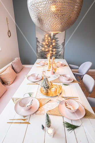 Festively set dining table below spherical silver lamps