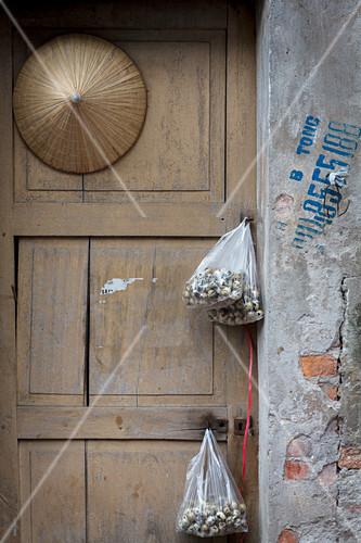 Bags of quail eggs hanging in a doorway Hanoi Vietnam