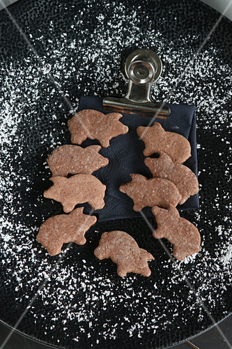 Pig-shaped gluten-free biscuits on a black plate surrounded by a dusting of icing sugar