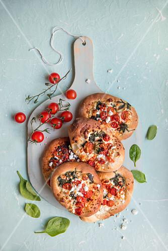 Feta cheese, spinach an tomatoe flt bread on a chopping board