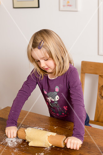 Little girl rolling out pastry