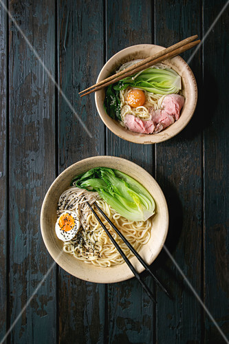 Asian dish with udon noodles with boiled egg, sesame, mushrooms, boc choy, sous vide pork meat served in ceramic bowls