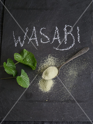 Wasabipulver und Wasabiblätter auf Schiefertafel mit Schriftzug