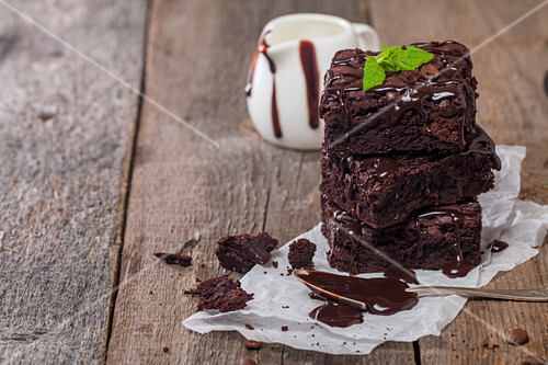Delicious chocolate brownie with mint on wooden table