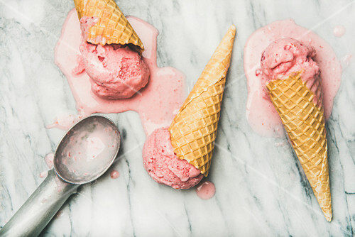 Yogurt strawberry ice cream in waffle cones over grey marble background