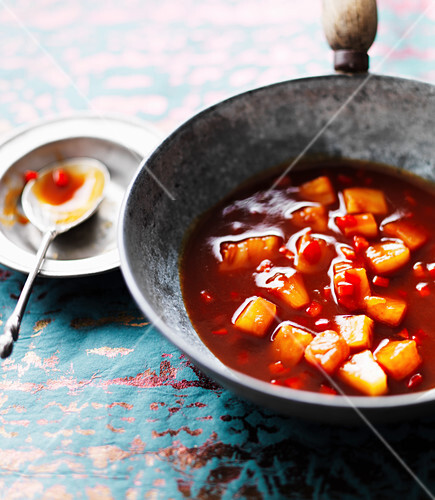 Sweet and sour sauce with pineapple, chillies and carrots in a wok