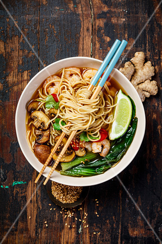 Asian soup with noodles (ramen), with miso paste, soy sauce, greens, mushrooms and shrimps prawn