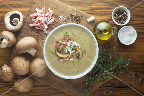 Cream of mushrooms soup with ingredients on a wooden surface