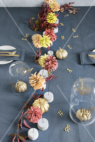 Table set in autumnal style with painted pumpkins and pine cones