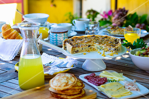 Brunch with quiche, pancakes, sausage, cheese and orange juice