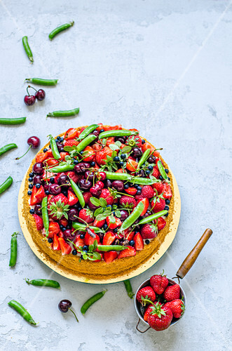 A fruit cake with strawberries, cherries, pea pods and blueberries