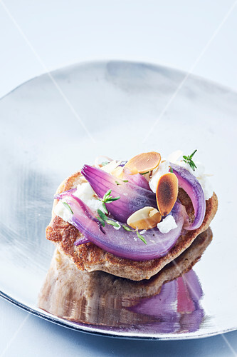 A blini topped with goat's cheese, red onions and roasted, flaked almonds