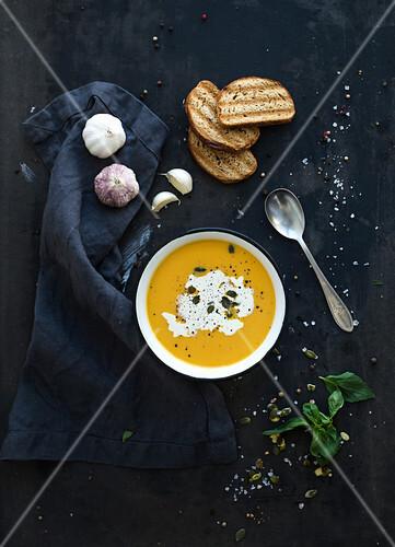 Kürbissuppe mit Sahne und Kürbiskernen, daneben Brot, Basilikum und Knoblauch