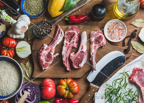 Raw uncooked lamb meat ribs, rice, oil, spices and vegetables