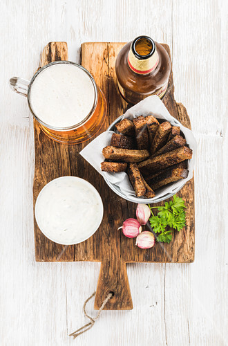 Beer snack set - Pint of pilsener in mug, open glass beer bottle, rye bread croutons with garlic cream cheese sauce