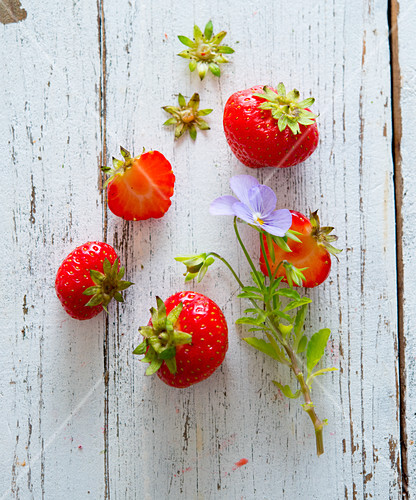 Fresh strawberries and a tufted pansy on a wooden surface
