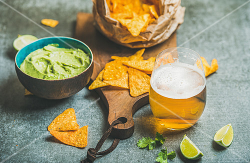 Mexican corn chips, guacamole sauce and glass of wheat beer