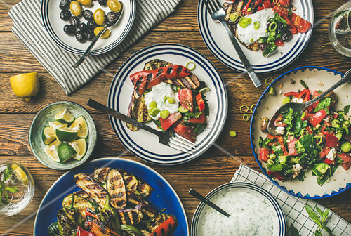 Healthy vegan dinner table setting - Fresh salad, grilled vegetables with yogurt sauce, pickled olives, lemon water