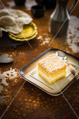 Slice of the sponge cake with lemon cheese cream and coconut shreds