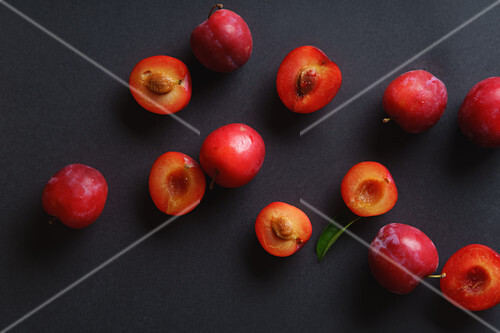 Red sweet cherry plums on dark background, whole and halved
