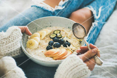 Woman in woolen sweater and jeans holding plate of vegan almond milk oatmeal porridge with berries, fruit and almonds