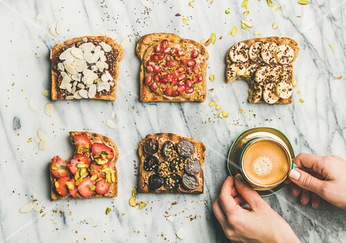 Vegan wholegrain toasts with fruit, seeds, nuts, peanut butter, cup of espresso and woman hands