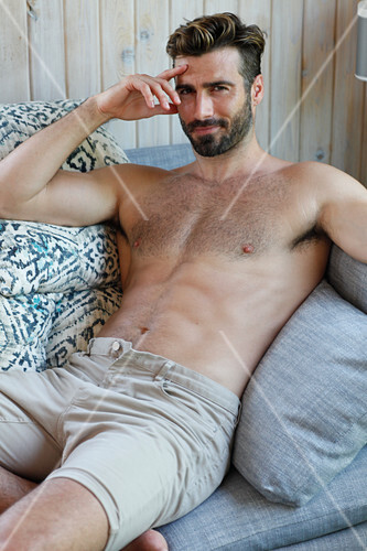 A young topless man lying on a sofa wearing shorts