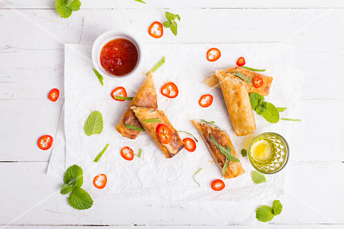 Spicy spring rolls served with fresh chili peppers, fresh mint and spicy sauce