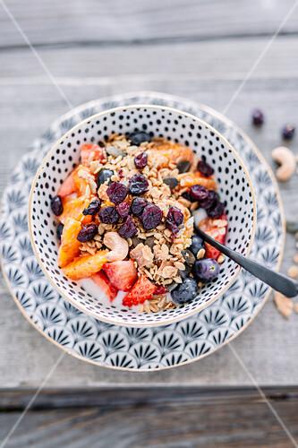 Vegan muesli with coconut yoghurt, cranberries, strawberries, blood oranges and blueberries