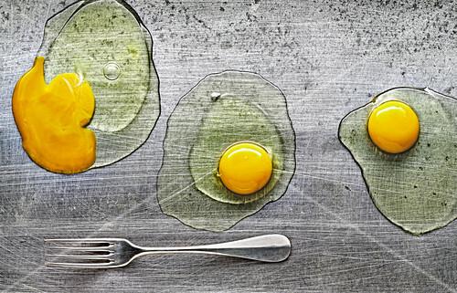 Food-Art: Drei aufgeschlagene Eier auf Metallplatte