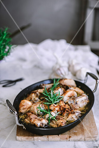 Pan with tasty roasted chicken with rosemary on table.
