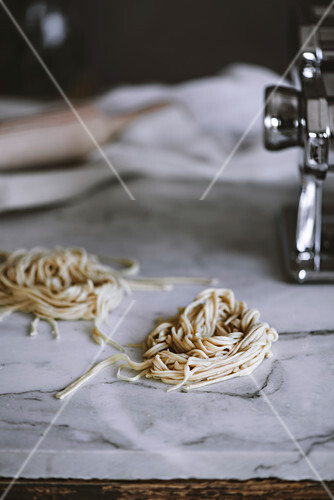 Two piles of raw noodles lying on white marble tabletop