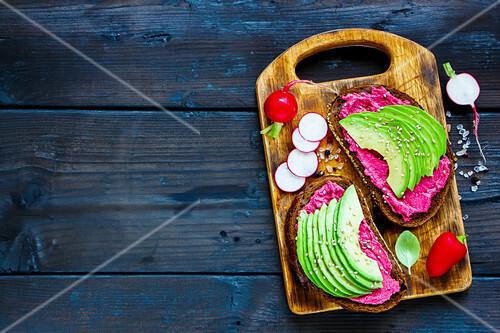Vegan breakfast avocado and beet rye sandwiches, fresh radishes and sweet pepper