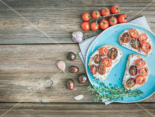 Belegte Brote mit Frischkäse, gebratenen Kirschtomaten, Knoblauch und Thymian