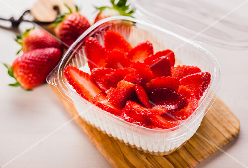 Close-up of plastic container filled with cream and sliced red strawberry
