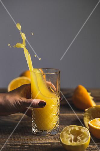 Frauenhand hält Glas mit spritzendem frischgepresstem Orangensaft