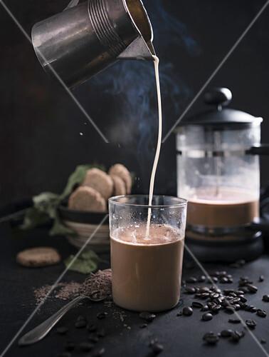 Haferdrink in ein Heißgetränk aus Kakao und Schokolade gießen