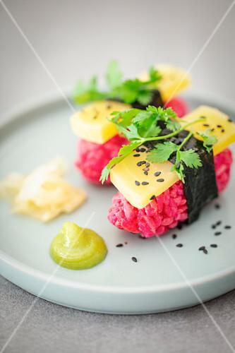 Vegan nigiri sushi with beetroot rice, yellow beetroot, nori and cilantro