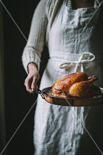 Frau serviert Brathähnchen mit Apfel-Birnen-Glasur in rustikalem Bräter