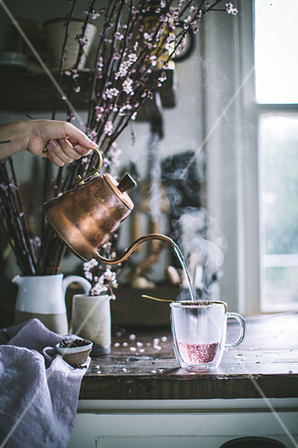 Hibiscus tea being poured from a copper kettle into a glass mug on a rustic wood kitchen countertop