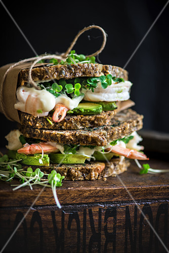 Prawn and avocado sandwich on a crunchy health bread with kombucha in the background