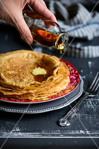 Egg pancakes with a drizzle of maple syrup and dollop of butter