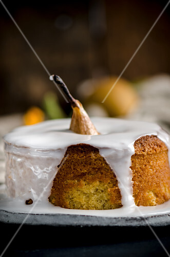 A vanilla cake with a whole baked pear and icing