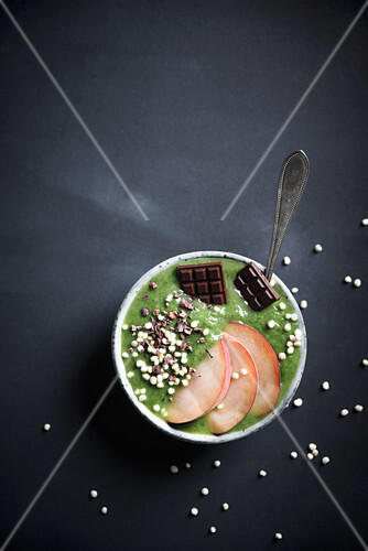 A green smoothie bowl with peaches, quinoa pops, cacao nibs and chocolate
