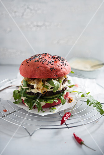 A burger with a beetroot bun, a black-bean patty, rocket, cucumber and remoulade
