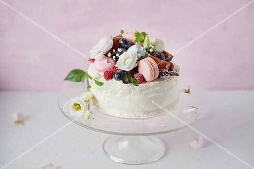 Festive cake decorated with macarons and berries
