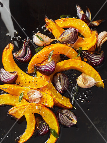 Oven-roasted pumpkin wedges with red onions and garlic (seen from above)