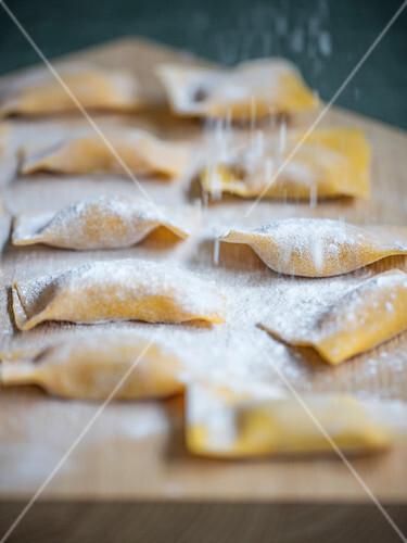 Tortelli di zucca (Kürbis-Nudeltaschen, Italien) mit Mehl bestauben