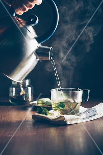 Heisses Wasser in eine Teetasse gießen