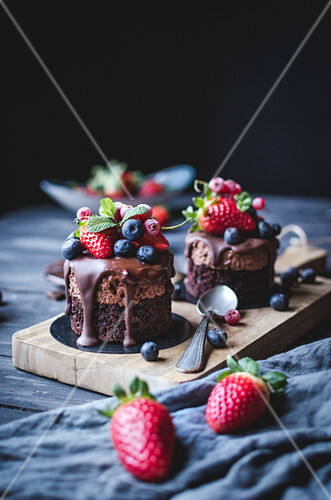 Tasty sweet chocolate cakes decorated with different berries